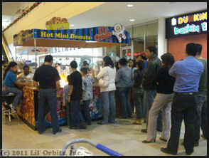A mini donut operation in Honduras showing the typical long lines of people waiting for donuts